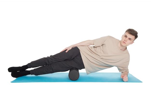 Przystojny mężczyzna pokazuje ćwiczenia za pomocą wałka z pianki
