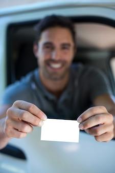 Przystojny mężczyzna pokazuje wizytówkę