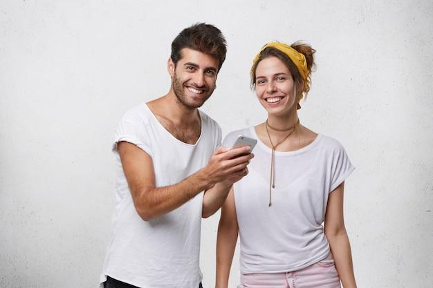 Przystojny mężczyzna pokazuje zdjęcia na telefonie komórkowym swojej ładnej dziewczynie
