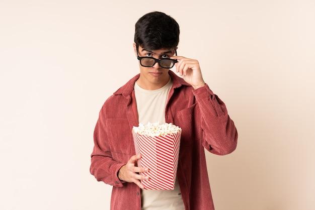 Przystojny mężczyzna ponad ścianą zaskoczony okularami 3d i posiadający duże wiadro popcorns