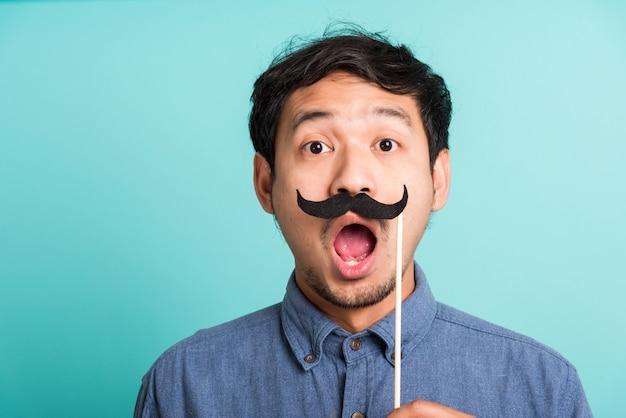 Przystojny mężczyzna pozowanie, trzymając kartę śmieszne wąsy lub rocznika fałszywe wąsy na ustach