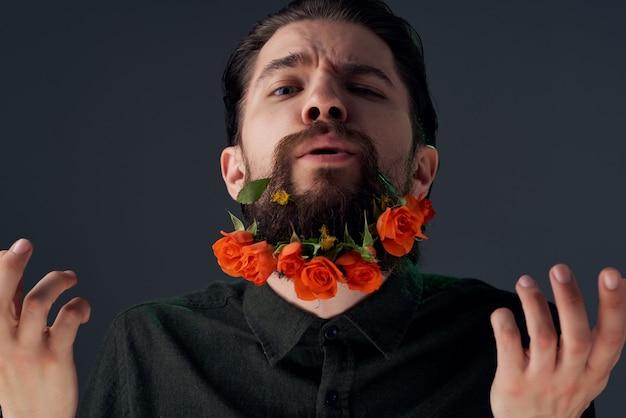 Przystojny mężczyzna pozuje kwiaty w ciemnym tle moda broda