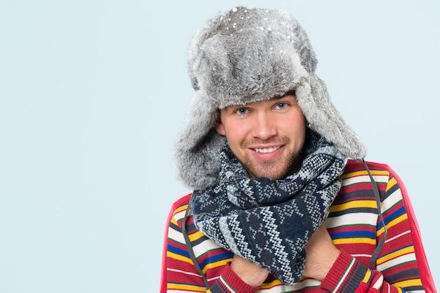 Przystojny mężczyzna pozuje podczas opadu śniegu