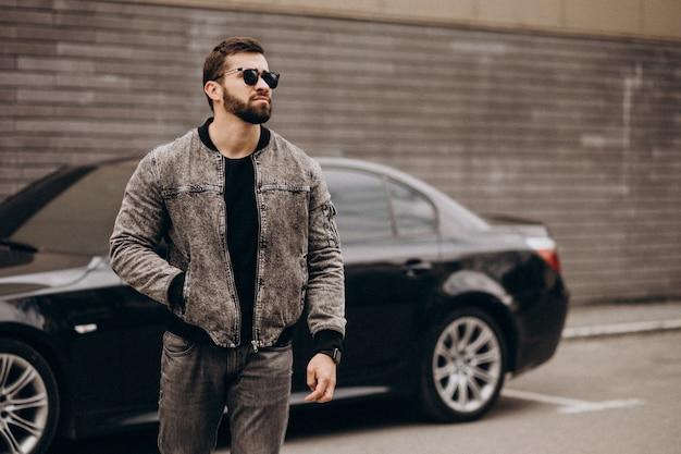 Przystojny mężczyzna pozuje samochodem w ulicie