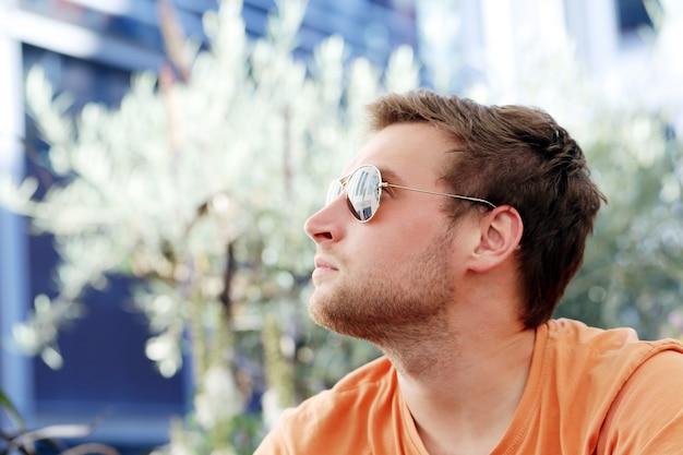 Przystojny mężczyzna pozuje w okularach przeciwsłonecznych
