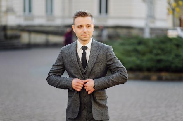 Przystojny mężczyzna pozuje w ślubnym kostiumu na ulicach