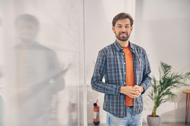 Przystojny mężczyzna pracownik w kraciastej koszuli, patrząc na kamerę i uśmiechając się
