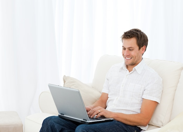 Przystojny mężczyzna pracuje na jego laptopie podczas gdy relaksujący na kanapie