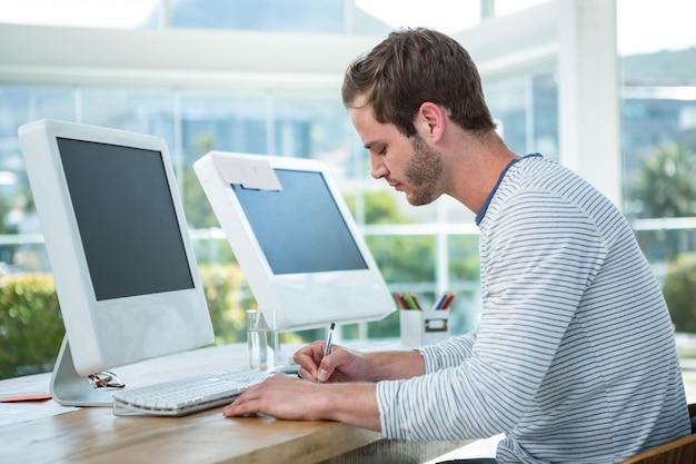 Przystojny mężczyzna pracuje na komputerze i bierze notatki w jaskrawym biurze