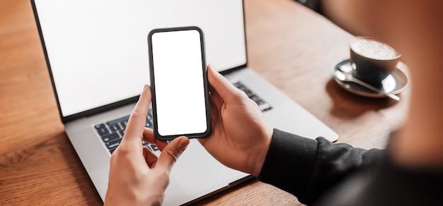 Przystojny mężczyzna pracuje na laptopie w miejscu pracy. biznesmen wpisywanie informacji na komputerze przy stole pracy z kawą i telefonem
