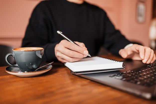 Przystojny mężczyzna pracuje na laptopie w miejscu pracy. biznesmen wpisywanie informacji na komputerze przy stole pracy z kawą