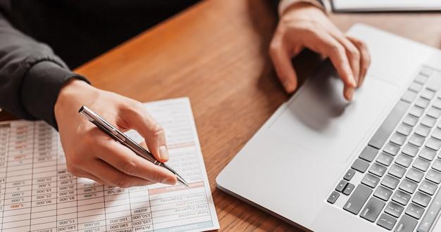 Przystojny mężczyzna pracuje na laptopie w miejscu pracy. biznesmen wpisywanie informacji na komputerze przy stole w pracy z notatnika