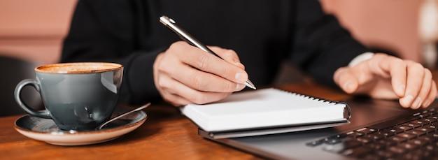Przystojny mężczyzna pracuje na laptopie w miejscu pracy.