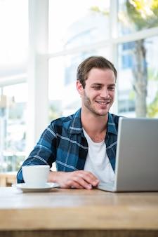 Przystojny mężczyzna pracuje na laptopie z filiżanką kawy w jaskrawym biurze