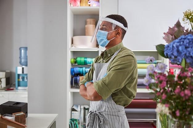 Przystojny mężczyzna pracuje w kwiaciarni przy kasie i nosi maskę i szkło dla ochrony podczas kwarantanny
