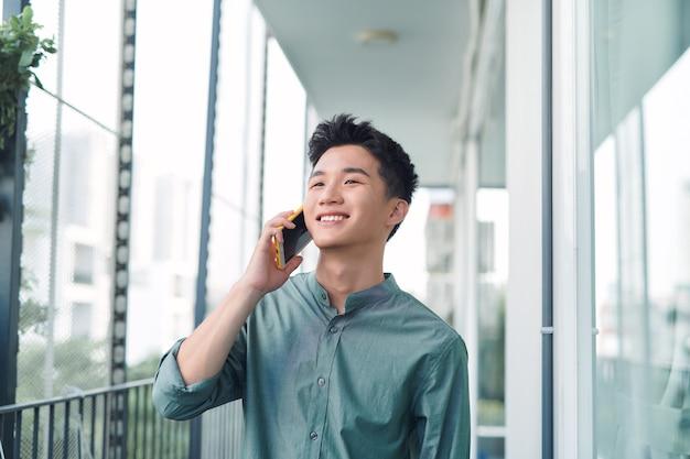 Przystojny mężczyzna prowadzi poważną rozmowę przez telefon komórkowy na zewnątrz na balkonie