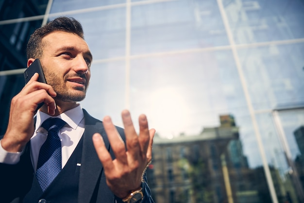 Przystojny mężczyzna przebywający na zewnątrz w pobliżu szklanego budynku, rozmawiając przez telefon komórkowy i patrząc poważnie