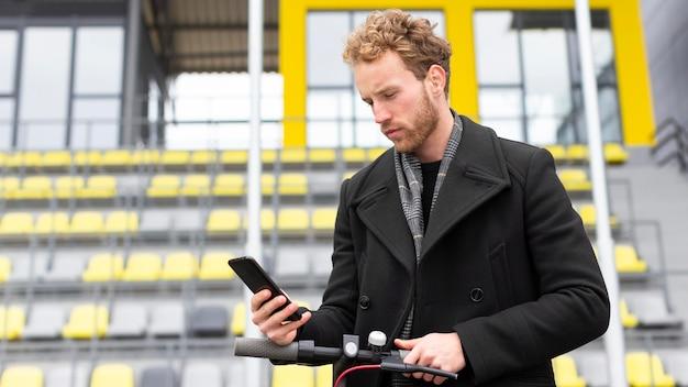 Przystojny mężczyzna przegląda swój telefon