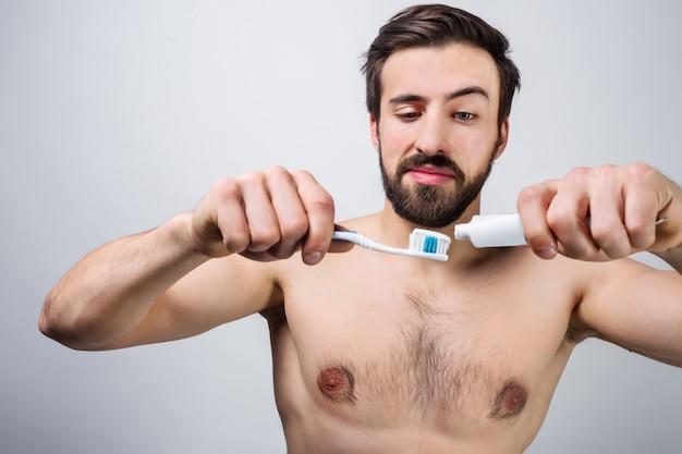 Przystojny mężczyzna przygotowuje się do mycia zębów. wydziela pastę do zębów na szczoteczkę. ścieśniać. wytnij widok.