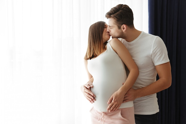 Przystojny mężczyzna przytula swoją uroczą ciężarną żonę w domu w domu