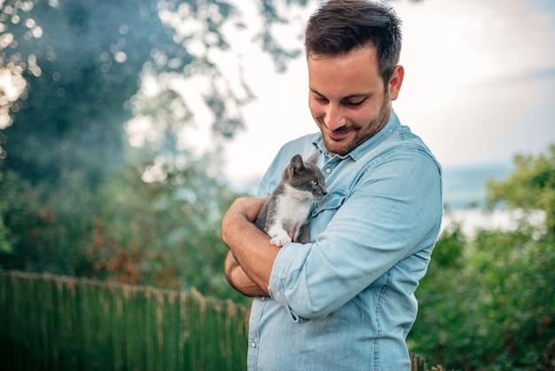 Przystojny mężczyzna przytulanie kota na zewnątrz.
