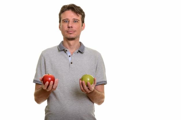 Przystojny mężczyzna rasy kaukaskiej gospodarstwa czerwone i zielone jabłko