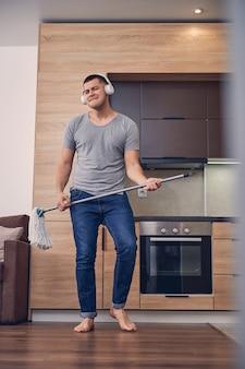 Przystojny mężczyzna rasy kaukaskiej w białych słuchawkach, stojący z kijem do mopa i śpiewający podczas mycia podłogi
