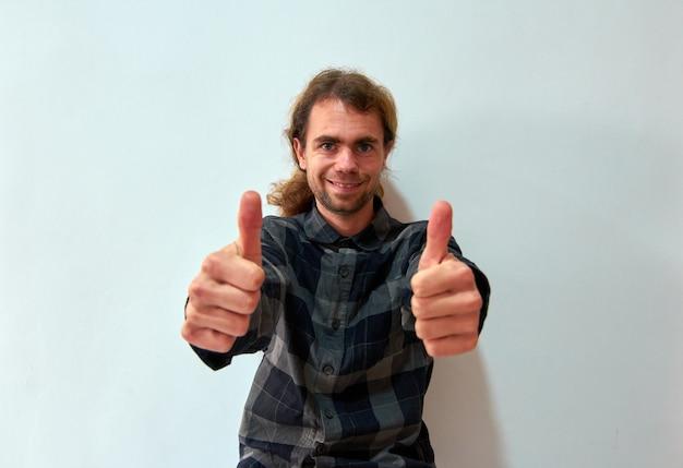 Przystojny mężczyzna rasy kaukaskiej z długimi włosami pokazując kciuki do góry obiema rękami na białym tle