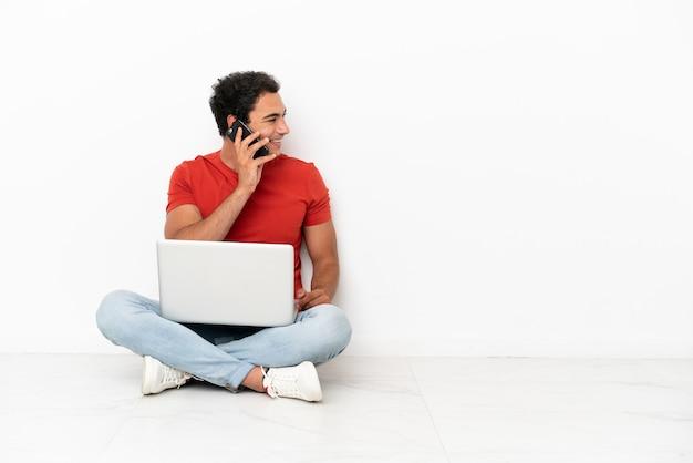 Przystojny mężczyzna rasy kaukaskiej z laptopem siedzącym na podłodze, prowadzącym z kimś rozmowę przez telefon komórkowy