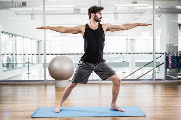 Przystojny mężczyzna robi joga na macie w studiu