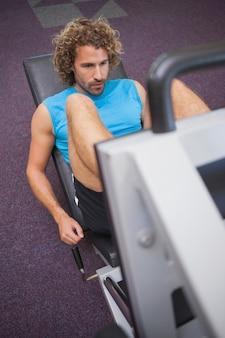 Przystojny mężczyzna robi nóg prasom w gym