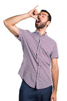 Przystojny mężczyzna robi pijany gest