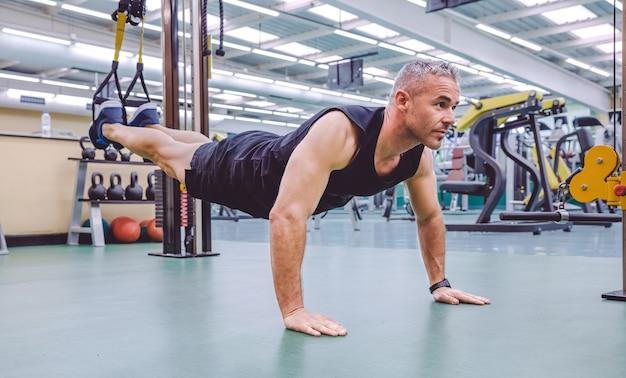 Przystojny mężczyzna robi twardy trening zawieszenia z pasami fitness w centrum fitness. koncepcja zdrowego i sportowego stylu życia.