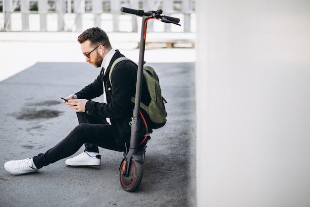Przystojny mężczyzna robi zakupy online na telefonie na hulajnoga