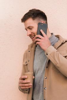Przystojny mężczyzna rozmawia przez telefon i trzymając kubek kawy