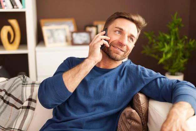 Przystojny mężczyzna rozmawia przez telefon komórkowy w domu
