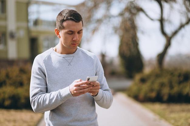 Przystojny mężczyzna rozmawia przez telefon na zewnątrz w parku