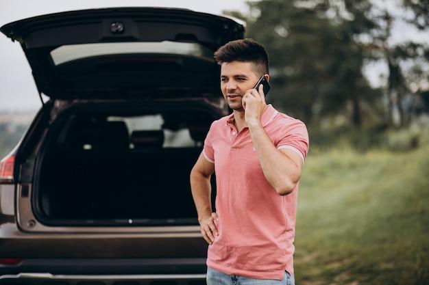 Przystojny mężczyzna rozmawia przez telefon przy samochodzie
