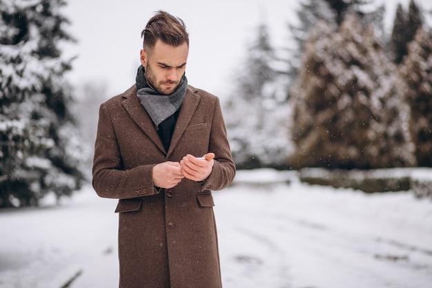 Przystojny mężczyzna rozmawia przez telefon w winter park