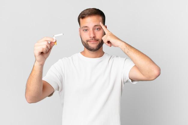 Przystojny mężczyzna rzuca palenie złamanym cygarem