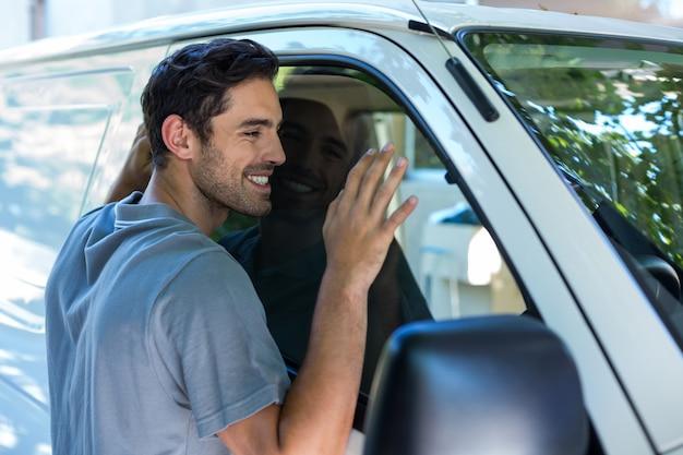 Przystojny mężczyzna ściska jego samochód