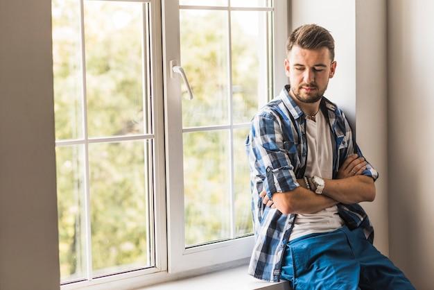 Przystojny mężczyzna siedzi blisko okno