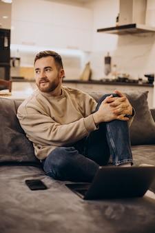 Przystojny mężczyzna siedzi na kanapie w domu i za pomocą gadżetów