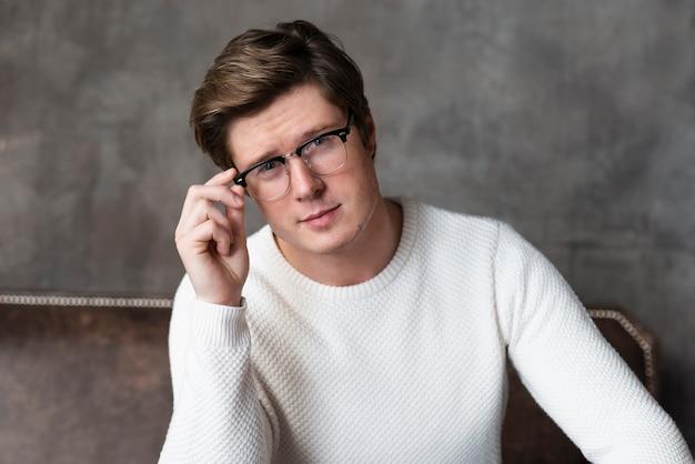 Przystojny mężczyzna siedzi na kanapie w okularach
