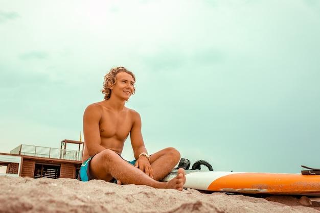Przystojny mężczyzna siedzi na plaży z białą deską surfingową puste czekać na falę do surfowania na brzegu oceanu