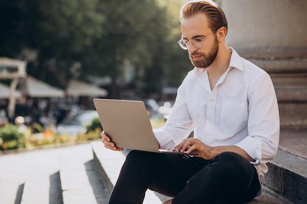 Przystojny mężczyzna siedzi na schodach i pracuje na komputerze