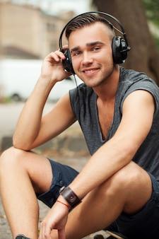 Przystojny mężczyzna siedzi na ulicy ze słuchawkami