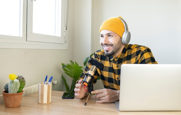 Przystojny mężczyzna siedzi w domowym biurze nagrywając podcast