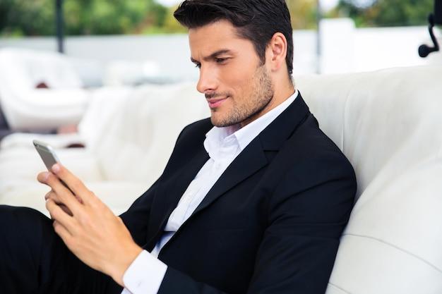 Przystojny mężczyzna siedzi w restauracji i przy użyciu smartfona
