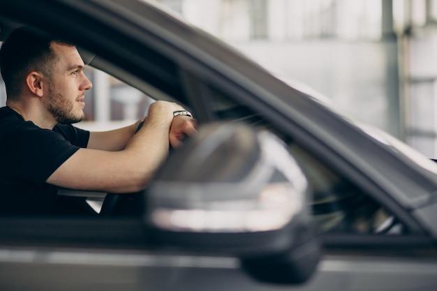Przystojny mężczyzna siedzi w samochodzie i testowanie go